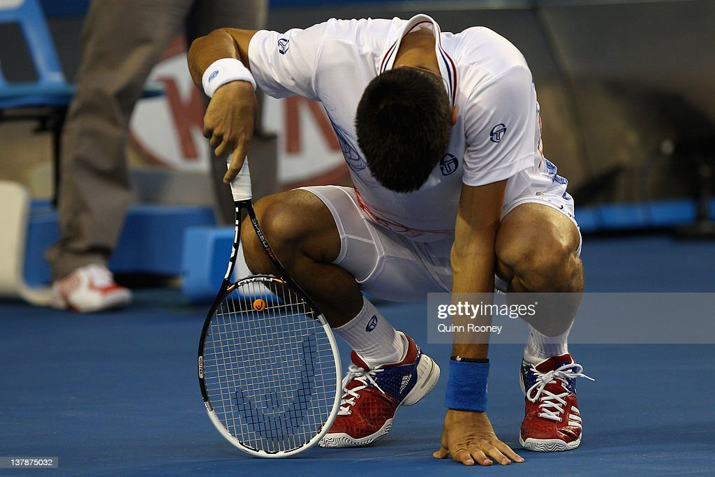 Novak Djokovic of Serbia crouches over in his men's final match against Rafael Nadal of Spain during day fourteen of the 2012 Australian Open at...