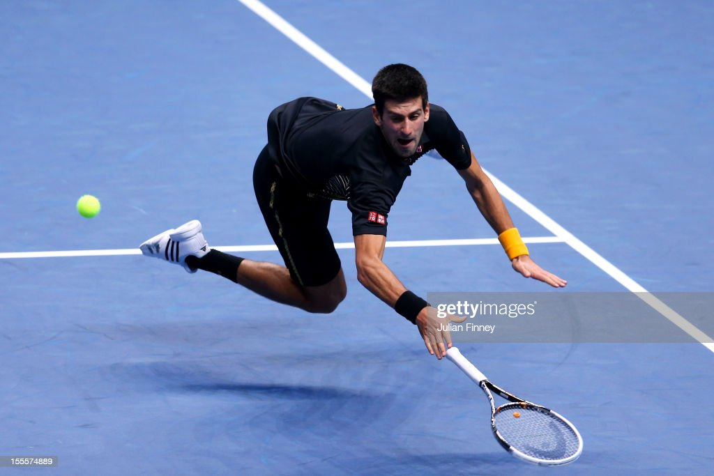 Novak Djokovic of Serbia dives to hit a backhand during the men's singles match against Jo-Wilfried Tsonga of France on day one of the ATP World Tour Finals at the O2 Arena on November 5, 2012 in London, England.