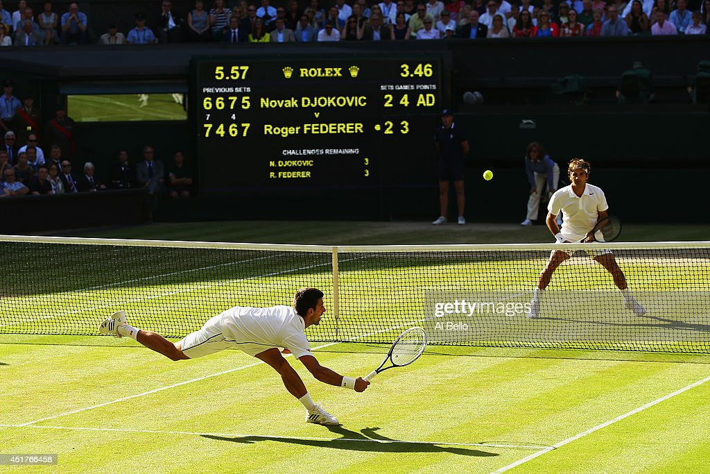 Novak Djokovic of Serbia dives to make a return as Roger Federer of Switzerland stands at the net during the Gentlemen's Singles Final match on day thirteen of the Wimbledon Lawn Tennis Championships at the All England Lawn Tennis and Croquet Club on July 6, 2014 in London, England.