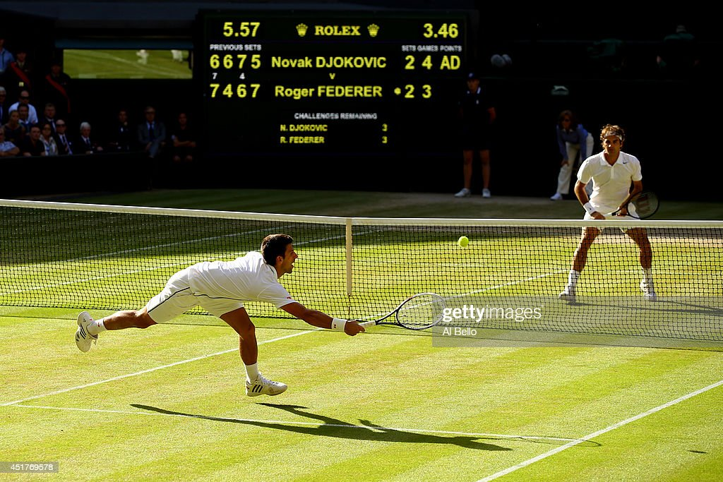 Novak Djokovic of Serbia dives to make a return as Roger Federer of Switzerland stands at the net during the Gentlemen's Singles Final match on day...