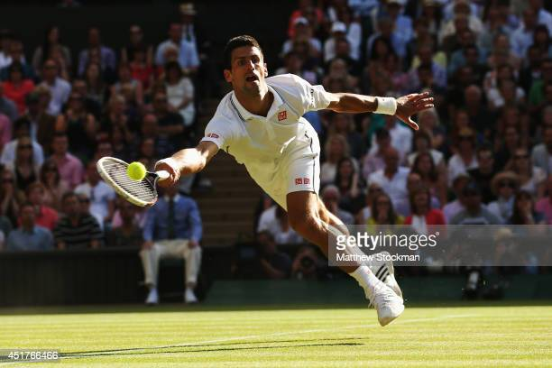 Novak Djokovic of Serbia dives to make a return during the Gentlemen's Singles Final match against Roger Federer of Switzerland on day thirteen of...