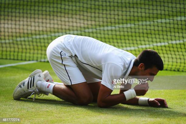 Novak Djokovic of Serbia eats some of the centre court grass as he kneels on the floor as he celebrates winning the Gentlemen's Singles Final match...
