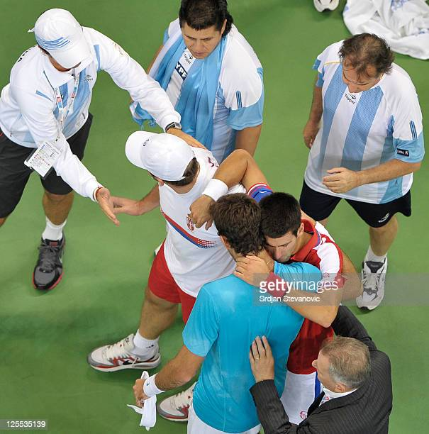 Novak Djokovic of Serbia falls after an injury during his Davis Cup semifinal match against Argentina's Juan Martin Del Potro at Belgrade Arena on...