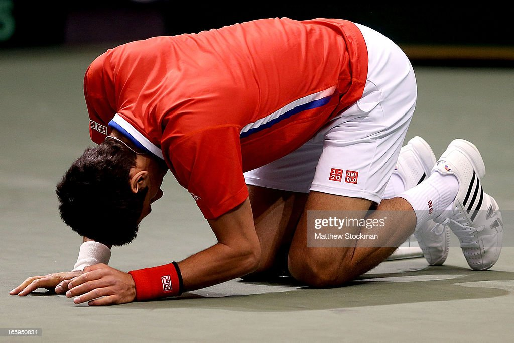 <a gi-track='captionPersonalityLinkClicked' href=/galleries/search?phrase=Novak+Djokovic&family=editorial&specificpeople=588315 ng-click='$event.stopPropagation()'>Novak Djokovic</a> of Serbia falls to the court in pain after injuring his ankle in the third game of the first set in the fourth rubber against Sam Querrey during the Davis Cup tie between the United States and Serbia at Taco Bell Arena on April 7, 2013 in Boise, Idaho.