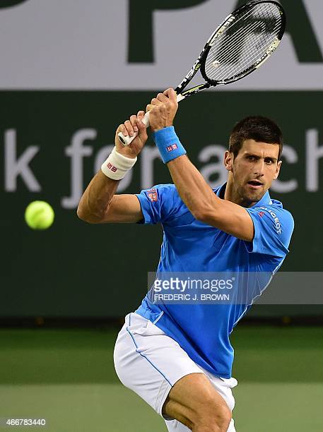 Novak Djokovic of Serbia hits a backhand return to John Isner of the US in their fourth round match at the BNP Paribas Tennis Open in Indian Wells...