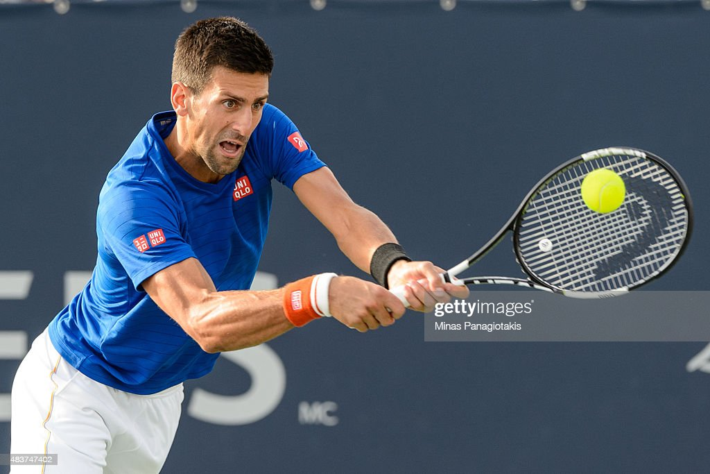 Novak Djokovic of Serbia hits a return against Rohand Bopanna of India and Florin Mergea of Romania during day three of the Rogers Cup at Uniprix...