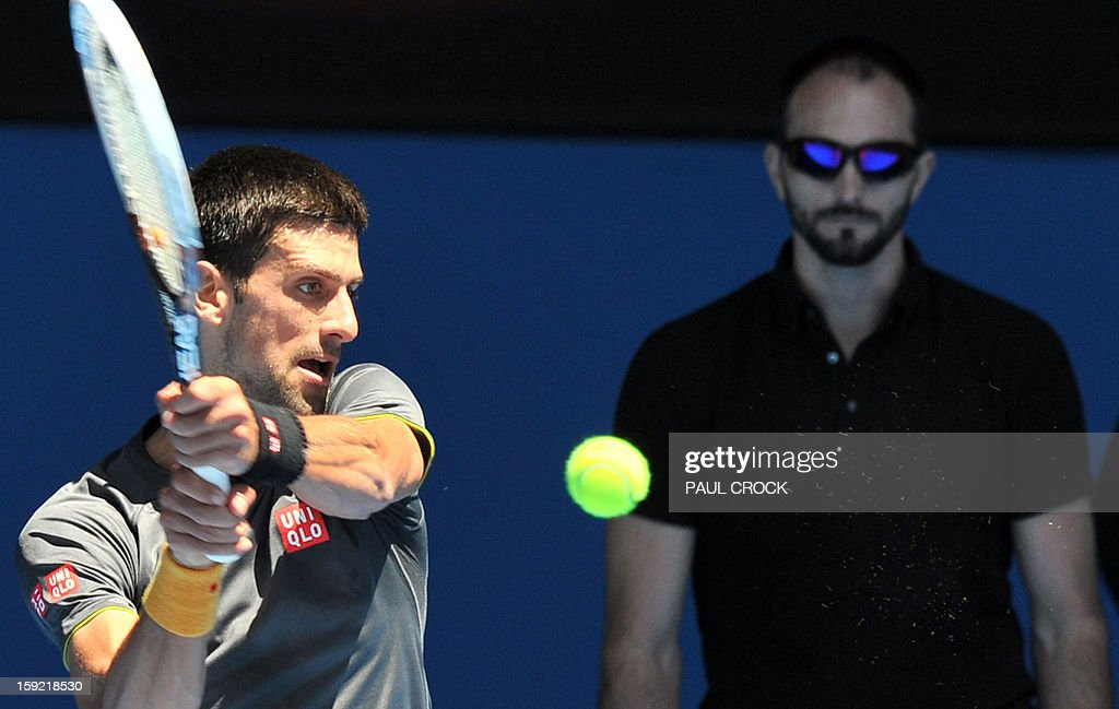 Novak Djokovic of Serbia (L) hits a return as a trainer watches on during a practice session for the upcoming Australian Open tennis tournament in Melbourne on January 10, 2013. The first Grand Slam tennis tournament of the year is set to run from January 14 to 27. AFP PHOTO / Paul CROCK IMAGE