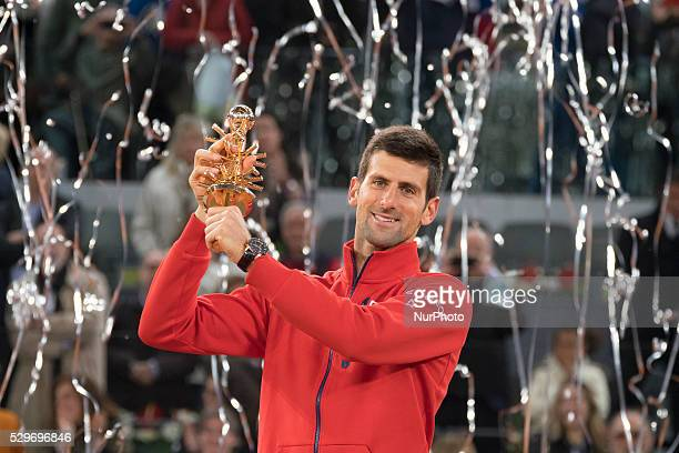 Novak Djokovic of Serbia holds aloft his winners trophy after his three set victory against Andy Murray of Great Britain in the mens final during day...