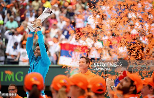 Novak Djokovic of Serbia holds aloft the Butch Buchholz trophy after his straight sets victory against Kei Nishikori of Japan in the mens final...