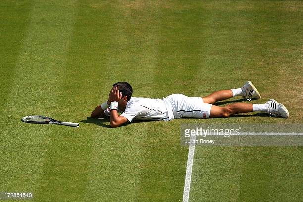 Novak Djokovic of Serbia holds his head in his hands after falling on the grass playing a forehand during the Gentlemen's Singles semifinal match...