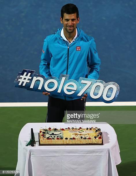 Novak Djokovic of Serbia holds his winners placard after beating Tunisian Malek Jaziri during their ATP tennis match on the third round of the Dubai...