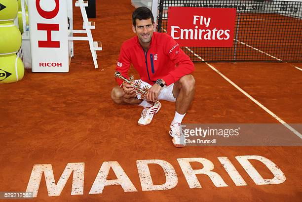 Novak Djokovic of Serbia holds his winners trophy by the Madrid centre court logo after his three set victory against Andy Murray of Great Britain in...