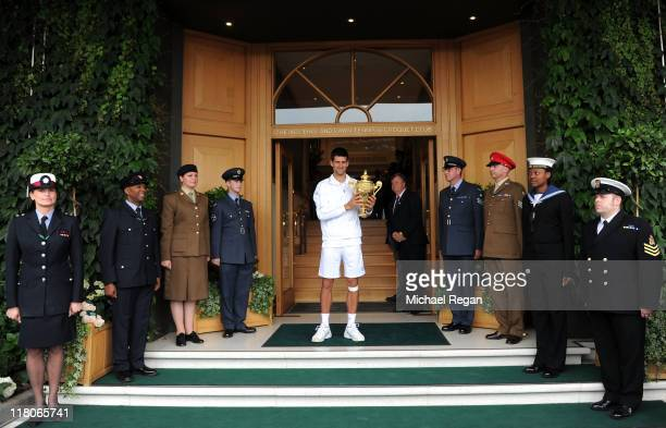 Novak Djokovic of Serbia holds the championship trophy outside the members entrance after winning his final round Gentlemen's match against Rafael...