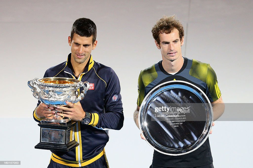 Novak Djokovic of Serbia holds the Norman Brookes Challenge Cup with runner up Andy Murray of Great Britain after Novak Djokovic won their men's...