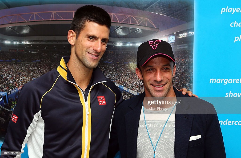 Novak Djokovic of Serbia holds the Norman Brookes Challenge Cup with footballer Alessandro Del Piero in the changerooms after winning his men's final match against Andy Murray of Great Britain during day fourteen of the 2013 Australian Open at Melbourne Park on January 28, 2013 in Melbourne, Australia.