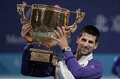 Novak Djokovic of Serbia holds the trophy aloft after defeating Carlos JoWilfried Tsonga of France in the Men's Singles Final of the China Open at...