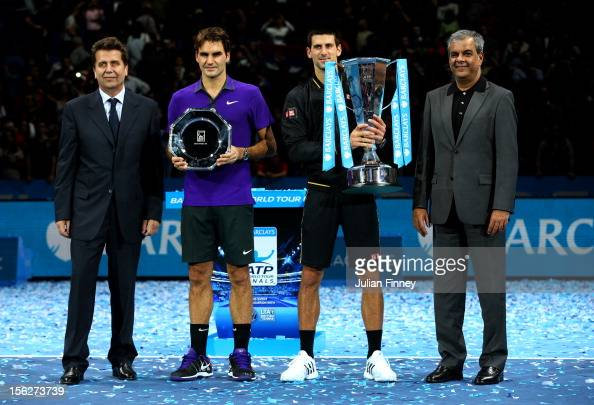 Novak Djokovic of Serbia holds the trophy next to Ashok Vaswani Chief Executive of Barclays Retail and Business Banking Brad Drewett Executive...