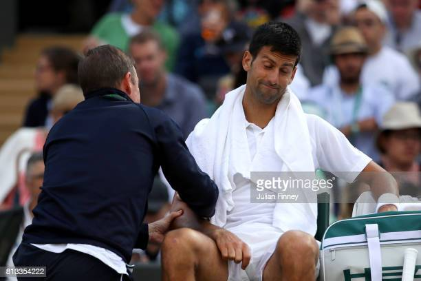 Novak Djokovic of Serbia is given treatment during the Gentlemen's Singles quarter final match against Tomas Berdych of The Czech Republic on day...