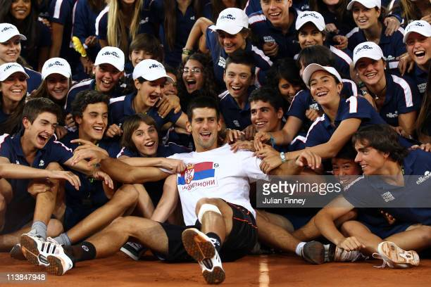 Novak Djokovic of Serbia is surrounded by ball boys and girls as he enjoys his win over Rafael Nadal of Spain after the final during day nine of the...