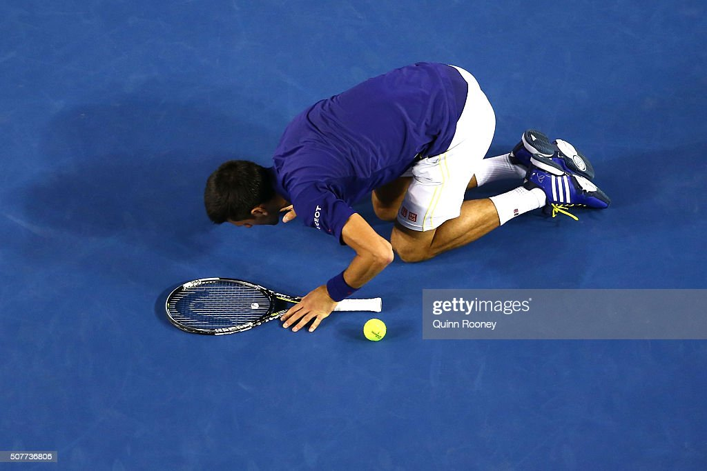 Novak Djokovic of Serbia kisses the ground at Rod Laver Arena after winning the Men's Singles Final over Andy Murray of Great Britain during day 14...