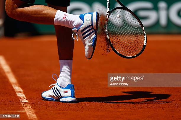 Novak Djokovic of Serbia knocks clay from his shoes in his Men's Semi Final match against Andy Murray of Great Britain on day fourteen of the 2015...