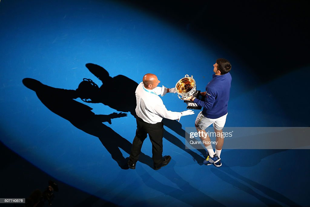 Novak Djokovic of Serbia leaves Rod Laver Arena with the Norman Brookes Challenge Cup after winning the Men's Singles Final over Andy Murray of Great...