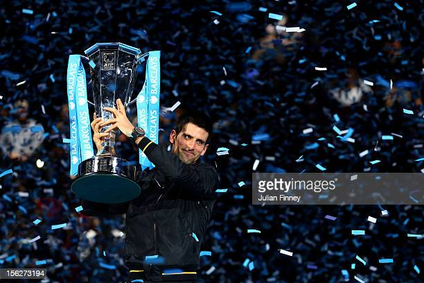 Novak Djokovic of Serbia lifts the trophy as he celebrates victory after his men's singles final match against Roger Federer of Switzerland during...