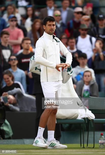 Novak Djokovic of Serbia looks on as he retires injured during the Gentlemen's Singles quarter final match against Tomas Berdych of The Czech...
