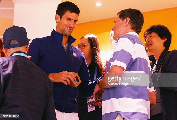 Novak Djokovic of Serbia passes out chocolates for the media during a press conference ahead of the 2016 Australian Open at Melbourne Park on January...