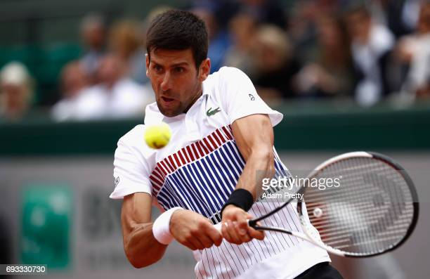 Novak Djokovic of Serbia plays a backhand during mens singles quarter finals match against Dominic Thiem of Austria on day eleven of the 2017 French...