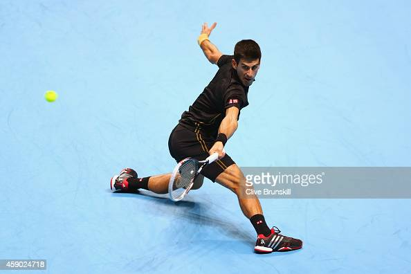 Novak Djokovic of Serbia plays a backhand in the singles semifinal match against Kei Nishikori of Japan on day seven of the Barclays ATP World Tour...