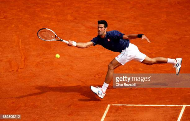 Novak Djokovic of Serbia plays a forehand against Gilles Simon of France in his second round match on day three of the Monte Carlo Rolex Masters at...