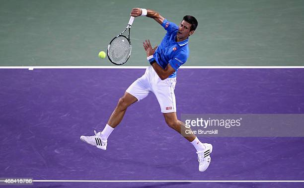 Novak Djokovic of Serbia plays a smash against David Ferrer of Spain in their quarter final during the Miami Open Presented by Itau at Crandon Park...