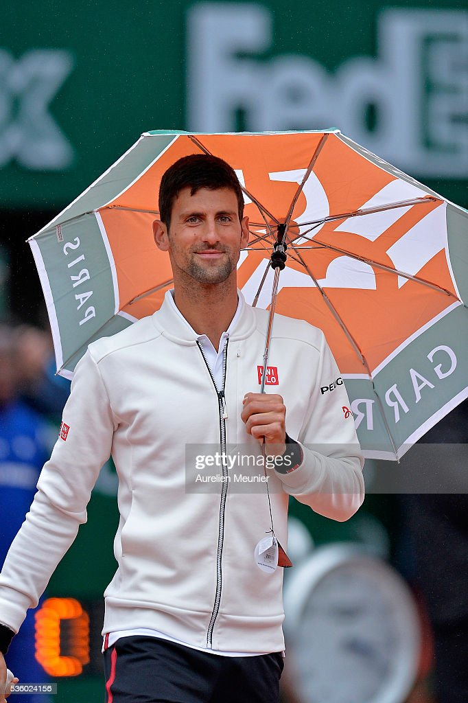 Novak Djokovic of Serbia plays with an umbrella during the rain break during his men's singles fourth round match against Roberto Bautista Agut of Spain on day ten of the 2016 French Open at Roland Garros on May 31, 2016 in Paris, France.