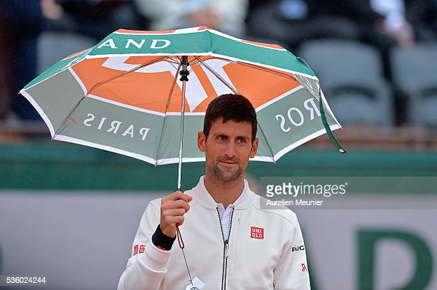 Novak Djokovic of Serbia plays with an umbrella during the rain break during his men's singles fourth round match against Roberto Bautista Agut of...