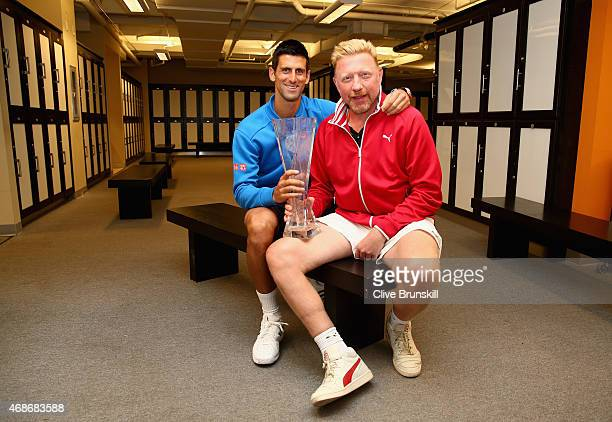 Novak Djokovic of Serbia poses for a locker room photograph with his coach Boris Becker and the Butch Bucholz trophy after his three set victory...