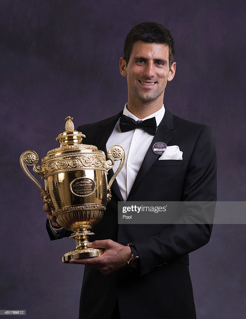 Novak Djokovic of Serbia poses with the Gentlemen's Singles Trophy at the Wimbledon Championships 2014 Winners Ball at The Royal Opera House on July 6, 2014 in London, England.