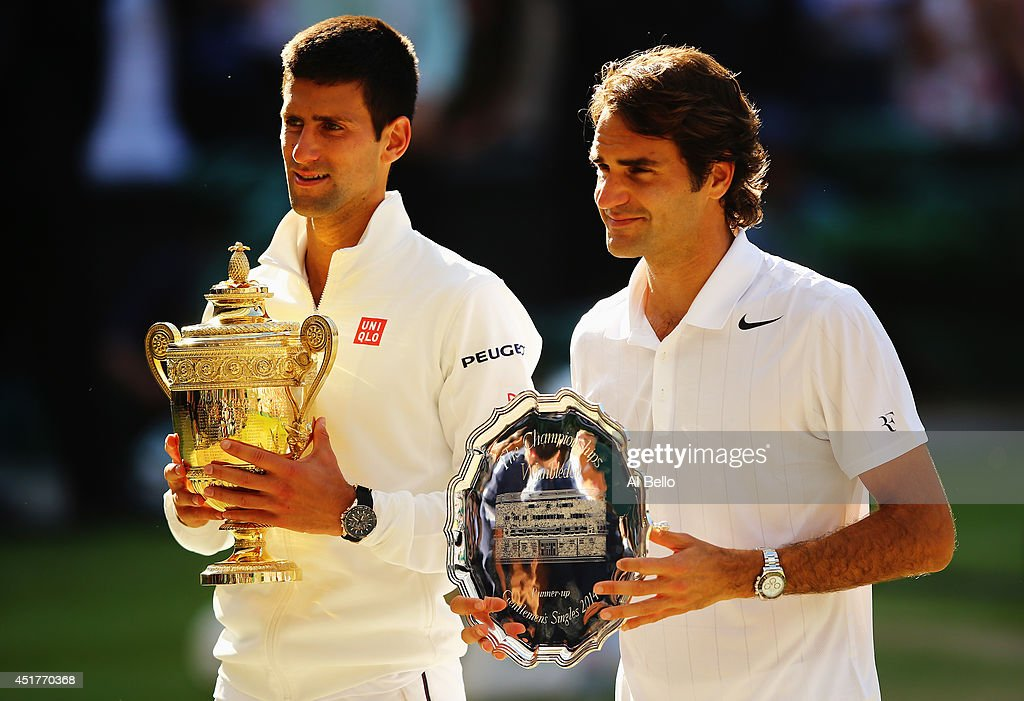 Novak Djokovic of Serbia poses with the Gentlemen's Singles Trophy next to Roger Federer of Switzerland following his victory in the Gentlemen's...