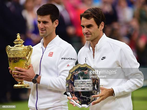 Novak Djokovic of Serbia poses with the Gentlemen's Singles Trophy next to Roger Federer of Switzerland following his victory in the Final Of The...