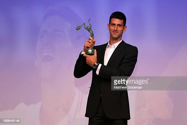 Novak Djokovic of Serbia poses with the Men's Singles World Champion award during the ITF World Champions Dinner at Pavillion D'Armenonville on June...