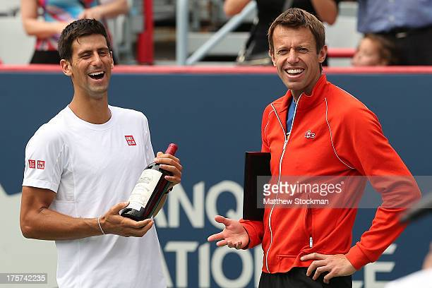 Novak Djokovic of Serbia presents Daniel Nestor of Canada with a bottle of wine commemorating his 25th year playing the tournament during the Rogers...