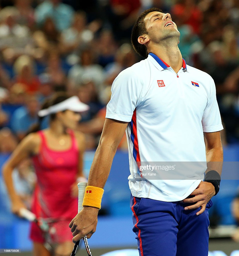 Novak Djokovic of Serbia reacts to missing a shot in the mixed doubles match partnered with Ana Ivanovic against Ashleigh Barty and Bernard Tomic of Australia during day five of the Hopman Cup at Perth Arena on January 2, 2013 in Perth, Australia.