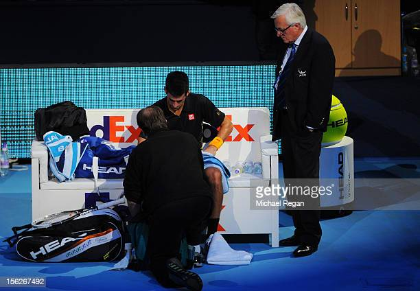 Novak Djokovic of Serbia receives assistance for an injury after diving to reach a shot during his men's singles final match against Roger Federer of...