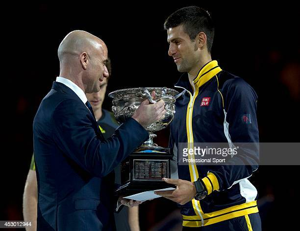 Novak Djokovic of Serbia receives the Norman Brookes Challenge Cup from Andre Agassi after winning his men's final match against Andy Murray of Great...