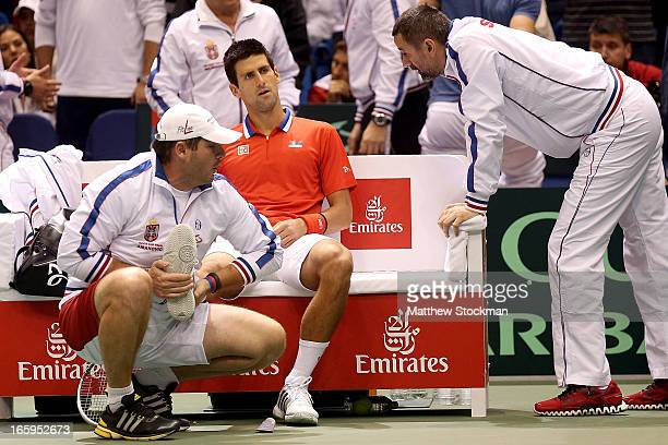 Novak Djokovic of Serbia receives treatment after injuring his ankle in the third game of the first set in the fourth rubber against Sam Querrey...