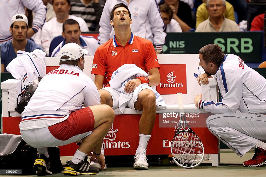 <a gi-track='captionPersonalityLinkClicked' href=/galleries/search?phrase=Novak+Djokovic&family=editorial&specificpeople=588315 ng-click='$event.stopPropagation()'>Novak Djokovic</a> of Serbia receives treatment after injuring his ankle in the third game of the first set in the fourth rubber against Sam Querrey during the Davis Cup tie between the United States and Serbia at Taco Bell Arena on April 7, 2013 in Boise, Idaho.