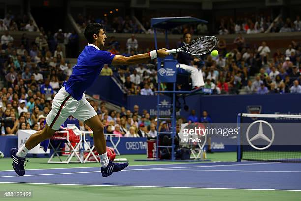 Novak Djokovic of Serbia returns a forehand shot to Roger Federer of Switzerland during their Men's Singles Final match on Day Fourteen of the 2015...