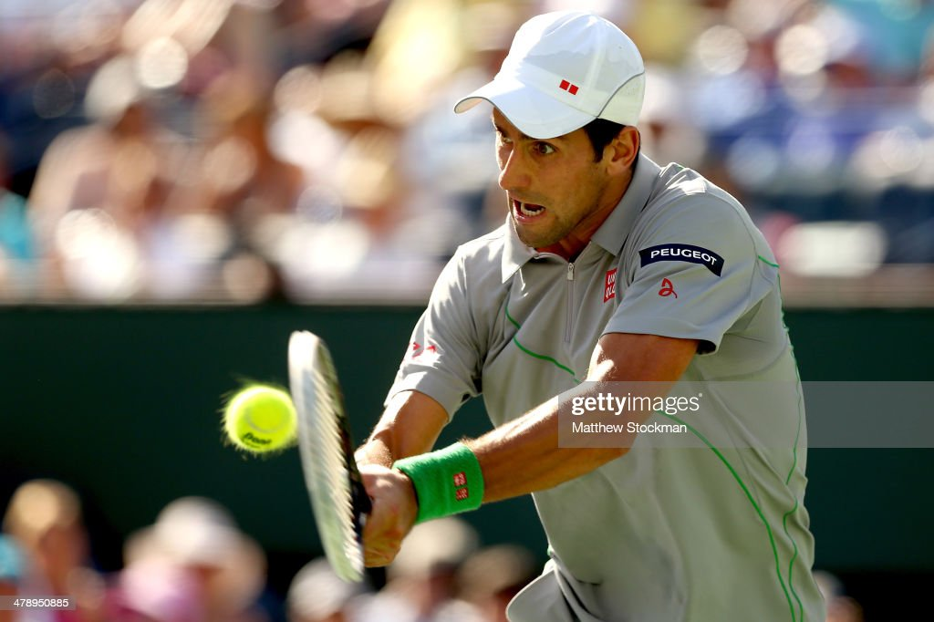 Novak Djokovic of Serbia returns a shot to John Isner during the semifinals of the BNP Parabas Open at the Indian Wells Tennis Garden on March 15...
