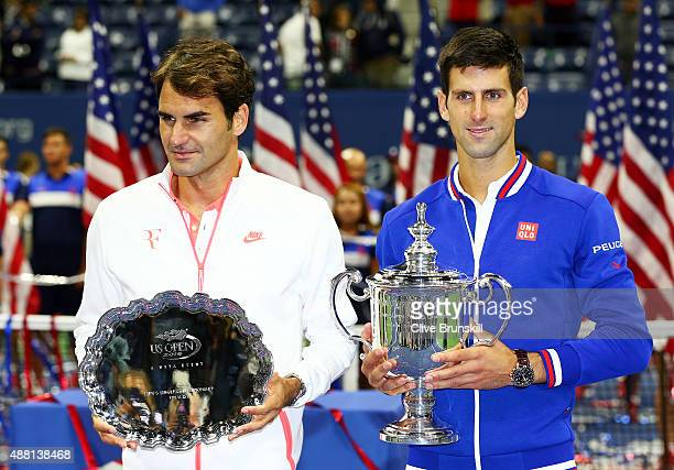Novak Djokovic of Serbia right and Roger Federer of Switzerland celebrate with thier trophies after their Men's Singles Final match on Day Fourteen...