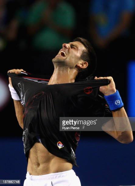 Novak Djokovic of Serbia rips his shirt off after winning championship point in his men's final match against Rafael Nadal of Spain during day...